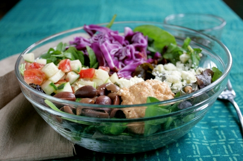 colorful mediterranean salad with hummus and harissa